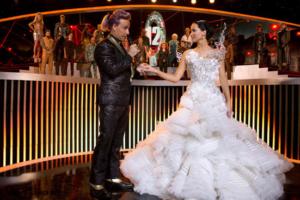 Host Caesar and a dressed up Katniss