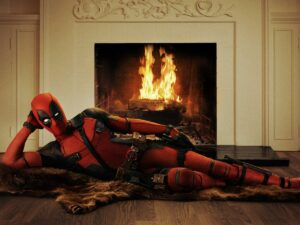 Deadpool lounging seductively by a fire.